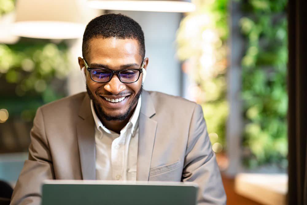 Male Executive. Happy black businessman using laptop, listening to music in wireless headphones, sitting at cafe, copyspace